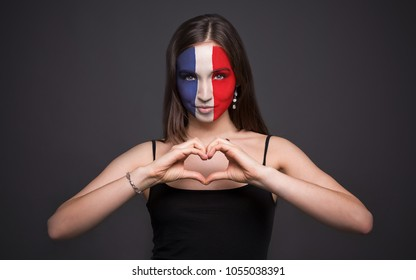 Portrait of a woman with the flag of France painted on her face. Football or soccer team fan, sport event, faceart and patriotism concept. Studio shot at gray background, copy space