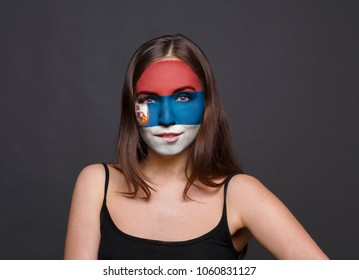 Portrait of a woman with the flag of Serbia painted on her face. Football or soccer team fan, sport event, faceart and patriotism concept. Studio shot at gray background, copy space