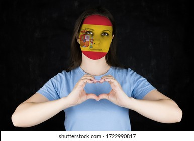 Portrait of a woman with the flag of Spain painted on her face. Football or soccer team fan, sport event and patriotism concept.
