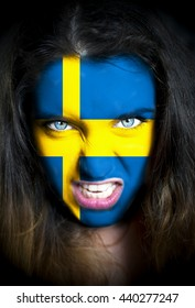 Portrait of a woman with the flag of the Sweden painted on her face.
