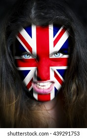 Portrait of a woman with the flag of the  United Kingdom painted on her face.