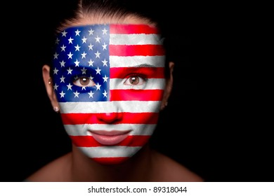 Portrait of a woman with the flag of the USA painted on her face.