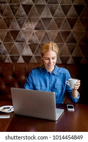 Portrait of woman freelancer working on laptop in cafe and drinking coffee