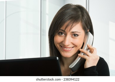 Portrait of a woman in front of her monitor while talking on the phone