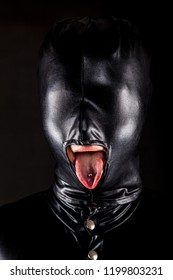 portrait of a woman with fully covered face behind a shiny rubber like head mask. she pokes out her tongue through a mouth opening showing her piercing