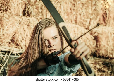 portrait of woman or girl archer with bow and arrow concentrated and aiming sunny summer outdoor on hay background