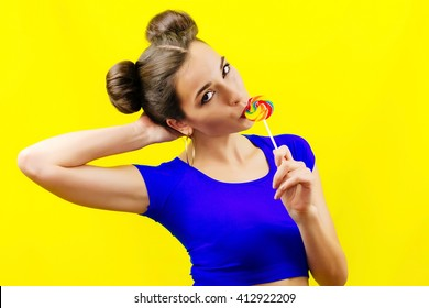 Portrait of woman, girl lick colorful round candy on the stick with beautiful make-up on yellow background. Colorful edgy fashion portrait of joyful playful woman with lollipop.