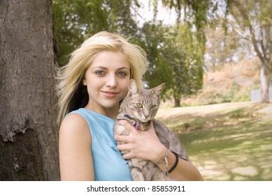Portrait of woman or girl with pet cat in garden