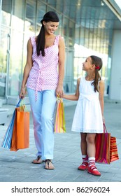 Portrait of a woman and girl walking with shopping bags