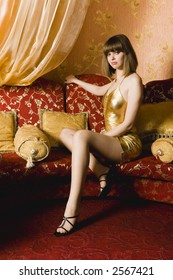 Portrait of woman in gold dress on the red couch