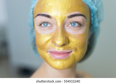portrait of a woman with gold facial mask