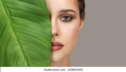 Portrait of woman and green leaf. Organic beauty. Gray background.
