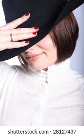 Portrait of a woman in hat closing her face