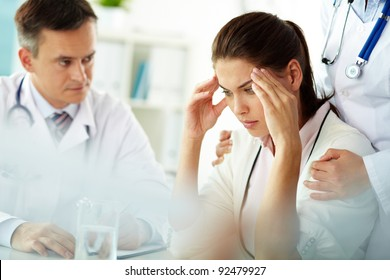 Portrait of woman with headache touching her temples with medical staff near by