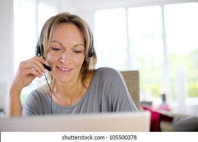 Portrait of woman with headset in front of laptop
