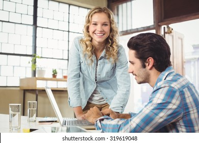 Portrait of woman helping male colleague working at office