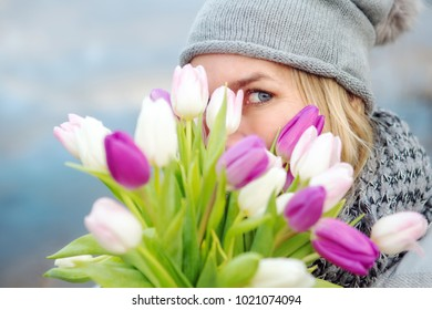 Portrait of woman hiding behind a bouquet of tulips