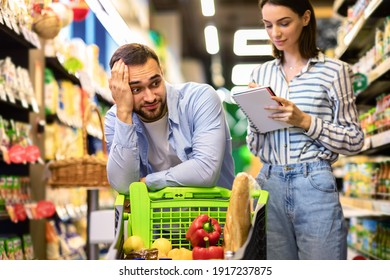 Portrait Of Woman Holding Checking Grocery Shopping List, Writing In Notebook, Tired Bored Funny Man Shocked By Price Leaning On Cart. Couple Buying Products In Supermarket With Trolley Full Of Food