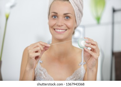 portrait of woman holding dental floss