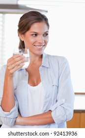 Portrait of a woman holding a glass of water in her kitchen