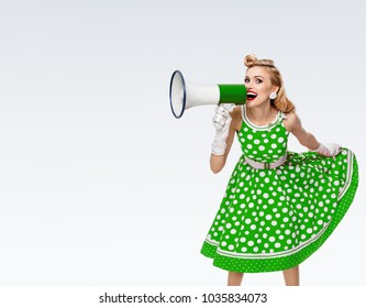 Portrait of woman holding megaphone, dressed in pin-up style green dress in polka dot and white gloves, on grey background, with blank copyspace area for  advertising text or slogan.
