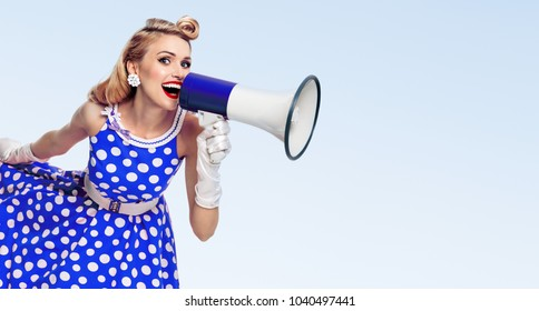 Portrait of woman holding megaphone, dressed in pin-up style dress in polka dot and white gloves, with copyspace area for slogan or advertising text message, on blue background. Caucasian blond model.