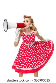 Portrait of woman holding megaphone, dressed in pin-up style red dress in polka dot and white gloves, isolated. Caucasian blond model posing in retro fashion and vintage concept studio shoot.