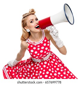 Portrait of woman holding megaphone, dressed in pin-up style red dress in polka dot and gloves, isolated on white background. Caucasian model posing in retro fashion vintage shoot. Square composition.