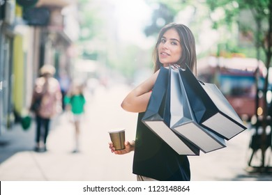 Portrait of woman holding paper bags and coffee on the street after shoping.