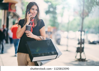 Portrait of woman holding paper bags and coffee on the street after shoping while using smart phone.