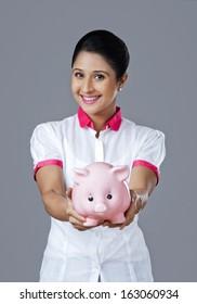 Portrait of a woman holding a piggy bank