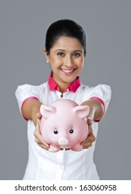 Portrait of a woman holding a piggy bank