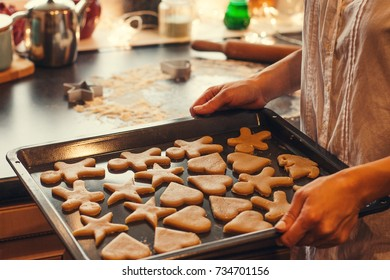 Portrait of woman holding a tray with raw biscuits ready for baking in the oven