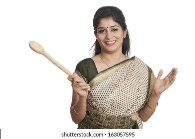 Portrait of a woman holding wooden ladle