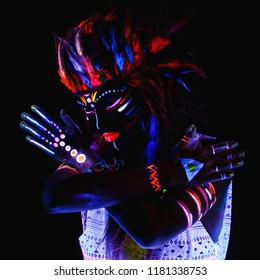 Portrait of woman in image of Red Indian with neon makeup, which made of fluorescent paint in ultraviolet light.