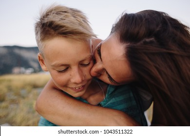 portrait of woman kissing her smiling son. soft focus on eyes