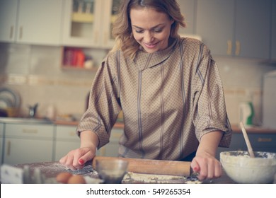 Portrait of woman in kitchen baking cookies .