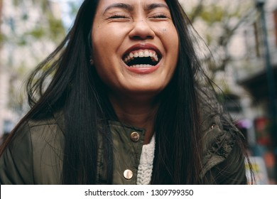 Portrait of a woman laughing with eyes closed. Cropped shot of an asian woman laughing standing outdoors.