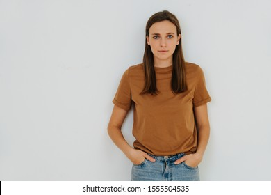 Portrait of a woman, leaning on the wall, with hands in pockets. Front view. She's of middle age, casually dressed, wears long brown hair behind ears and in front of her shoulders.
