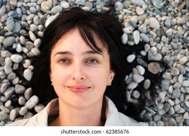 Portrait of woman lie on the stone beach