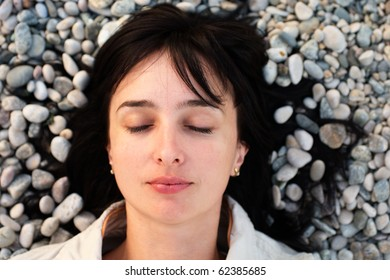 Portrait of woman lie on the stone beach with eyes closed