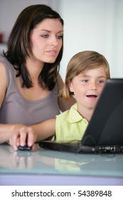 Portrait of woman and a little girl in front of a laptop computer