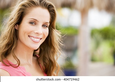 Portrait of woman with long brown hair outdoors