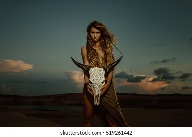 Portrait of woman with long dreadlocks hair hold in hand staff with cow skull with horn against sunset