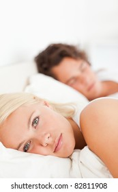 Portrait of a woman looking at the camera while her fiance is sleeping in their bedroom