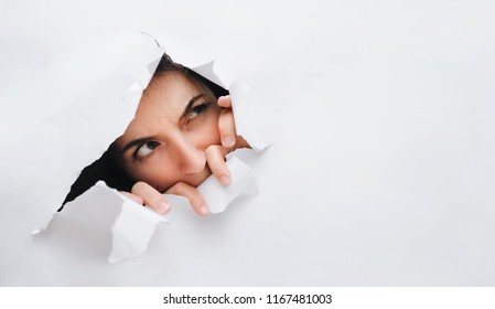 Portrait of a woman looking through the hole in white paper. Distrustful look. Women's curiosity and gossip. A jealous wife.