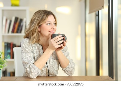 Portrait of a woman looking through a window drinking coffee sitting in a table at home