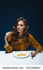 portrait of woman in luxury clothing with fork sitting at table with cheburek on plate with blue backdrop