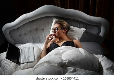 Portrait of woman lying on bed with a laptop and play with herself
