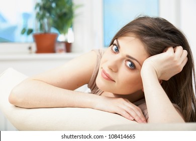 Portrait of woman lying on sofa. Casual style indoor shoot. Happy smiling relaxing girl on living room background.